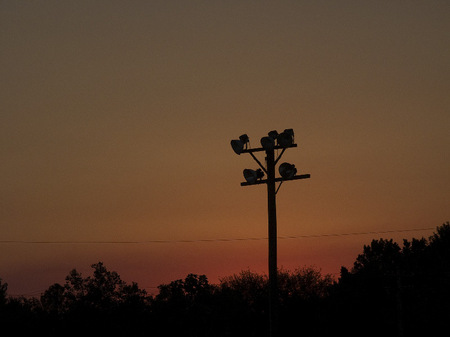 Athletic field light pole at dusk.