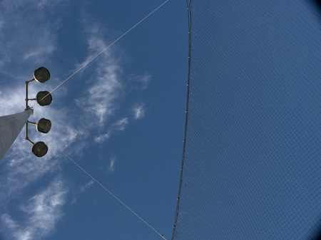 Baseball field light pole with clouds.
