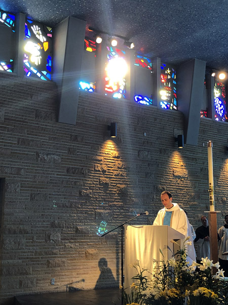 April 28   Beauty in the moment...the moment of a young man's first celebration of the Mass as a newly ordained priest while he delivers his first homily, the moment of the morning sun breaking through the stained glass to add a special feeling to this moment and memory.