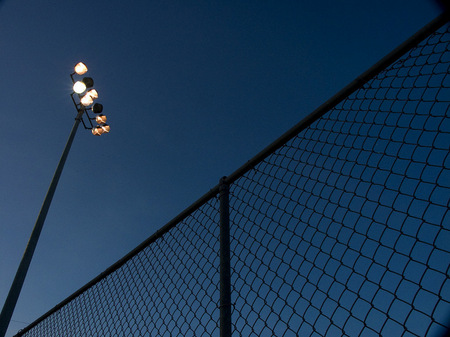 Baseball field light poles at twilight.