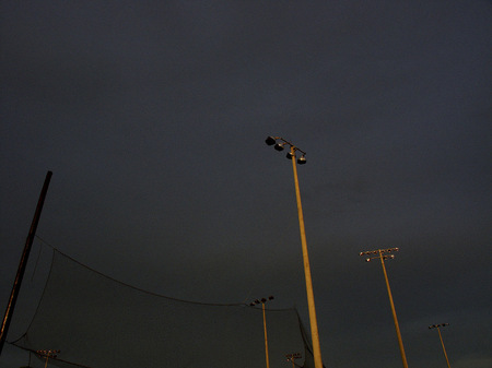 Baseball field light poles at sunset.