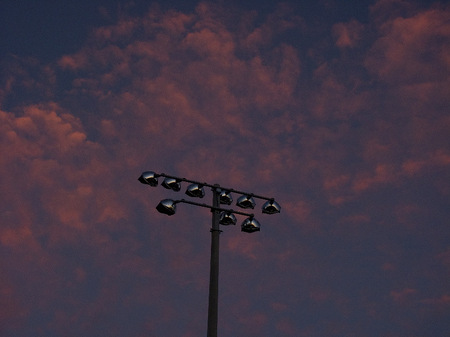 Athletic field light poles at sunset.