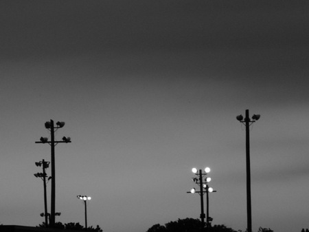 Little league light poles at dusk.